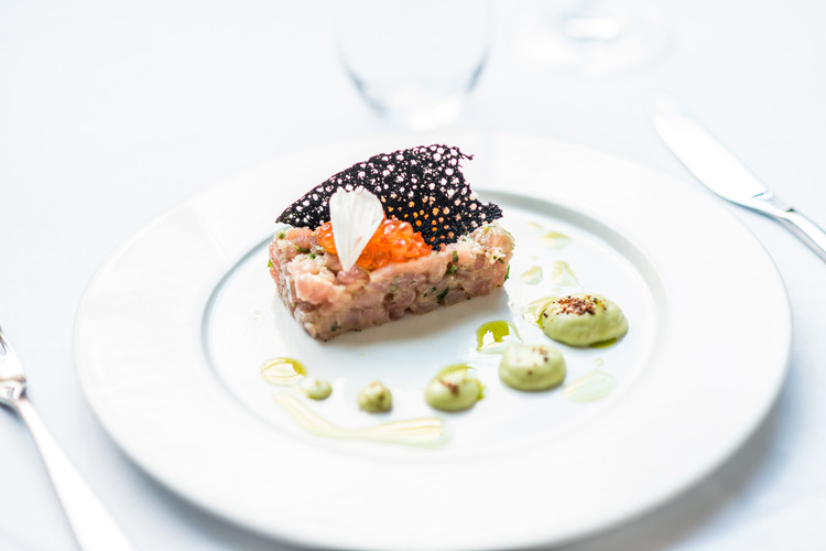A white china plate serving tuna tartare with avocado mousse and black ink tuille