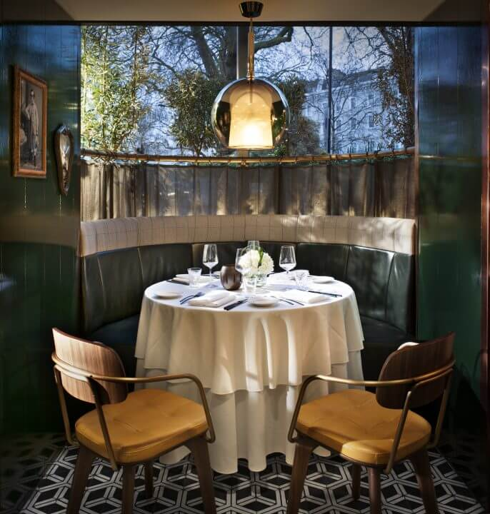Two mustard leather chairs sit in front of a round table set in a small window booth at il Pampero